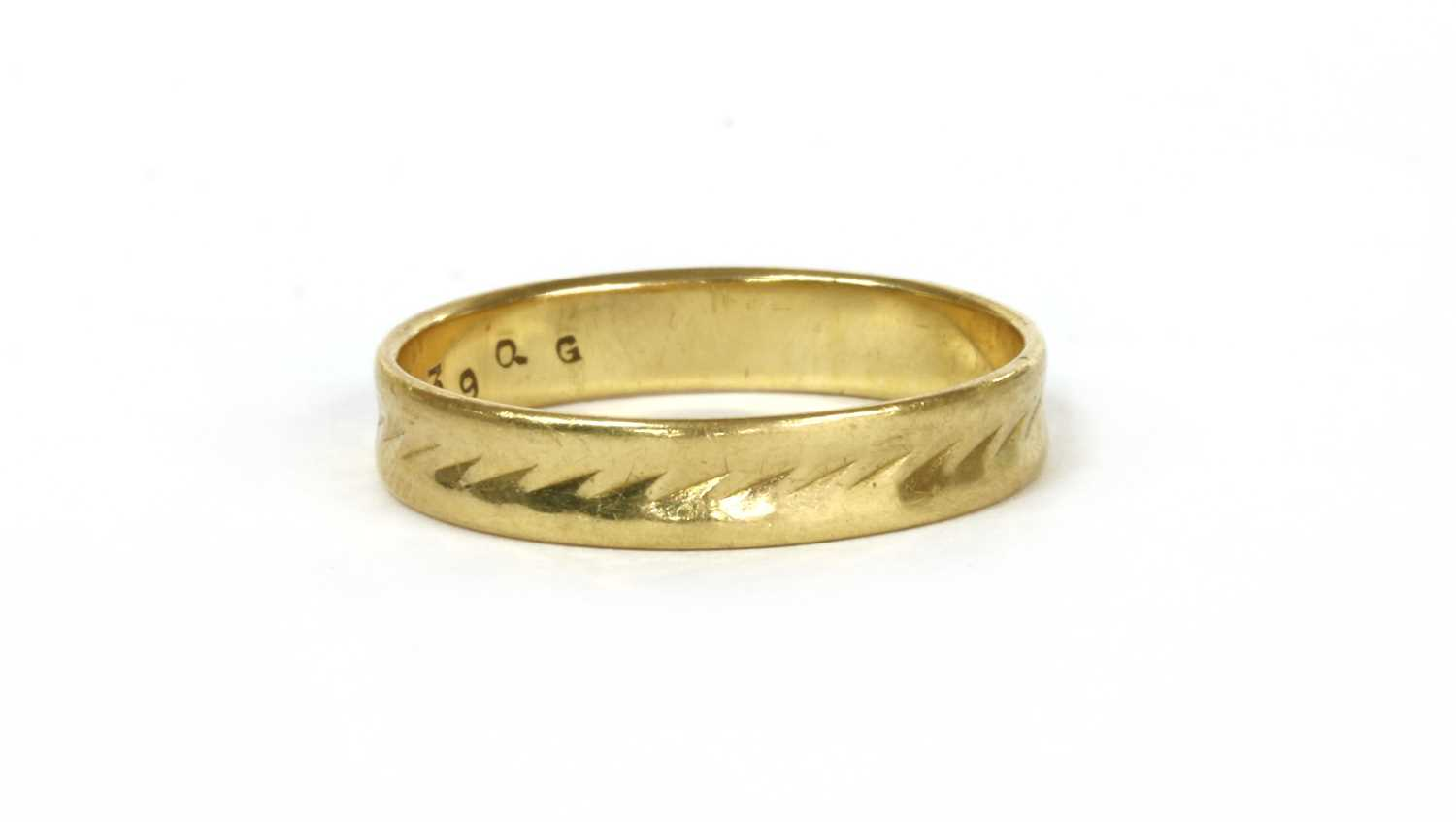 Lot 57 - An 18ct gold flat section patterned wedding ring
