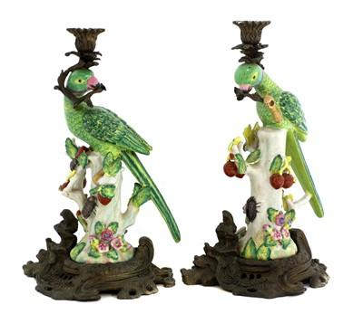 Lot 163 - A pair of gilt brass mounted pottery parrot candlesticks