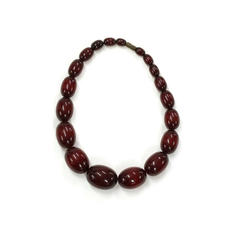 Lot 32 - A single row graduated cherry coloured Bakelite bead necklace