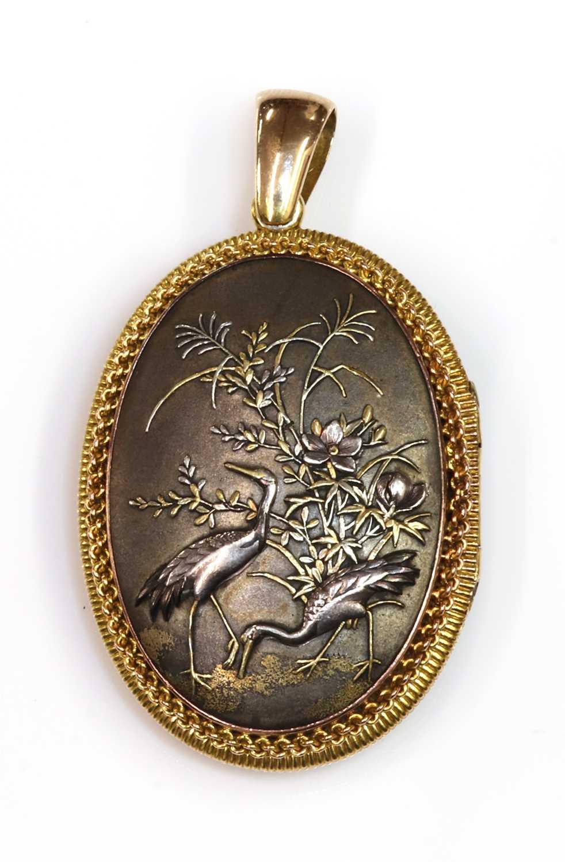 Lot 83 - A Shakudo double sided oval hinged locket, c.1880