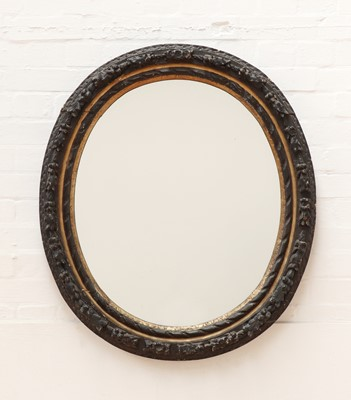 Lot 516 - A carved giltwood and ebonised oval wall mirror