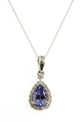 Lot 130 - A white gold tanzanite and diamond halo cluster pendant