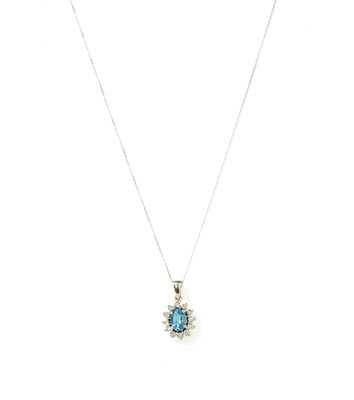 Lot 134 - A white gold blue topaz and diamond cluster pendant