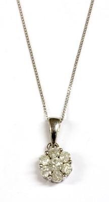 Lot 72 - A white gold diamond daisy cluster pendant