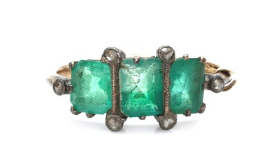 Lot 1016 - A gold and silver, emerald and diamond ring