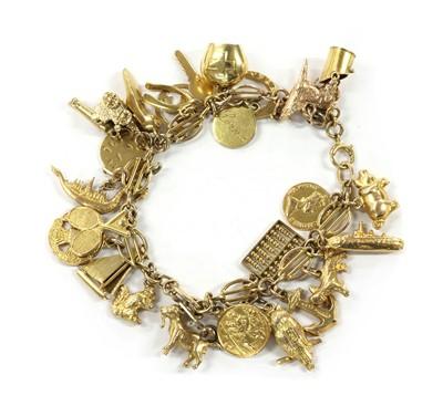 Lot 1098 - A gold charm bracelet