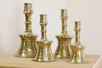 Lot 391 - A graduated set of four bell-shaped brass candlesticks