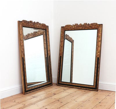 Lot 404 - A pair of ebonised and parcel-gilt mirrors