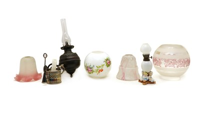 Lot 54 - A box of oil lamps and glass shades