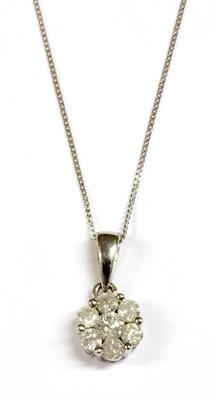 Lot 84 - A white gold diamond daisy cluster pendant